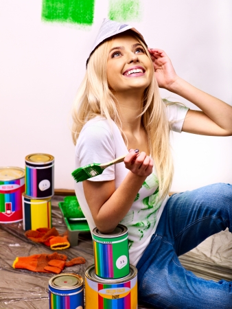 Happy woman paint wall at home. photo