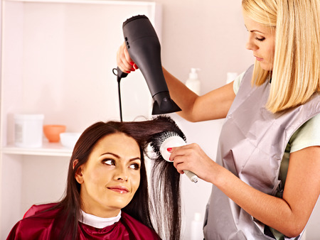 hairdryer: Woman at hairdresser with hairdryer.