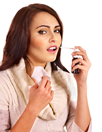 Young woman using throat spray. photo