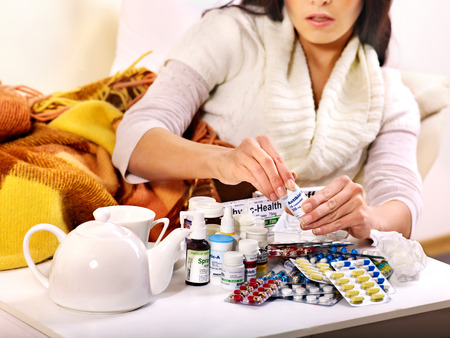 cold remedy: Woman with remedy having  flue in bed  Indoors