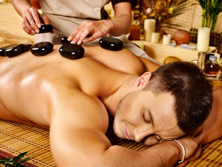 stone bowl: Man getting stone therapy massage in bamboo spa.
