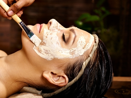 Woman having facial mask at ayurveda spa..