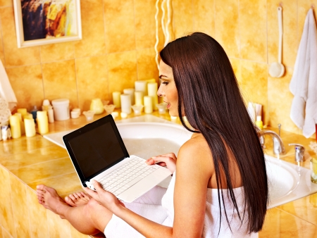 Woman relaxing at home luxury bath with laptop. photo