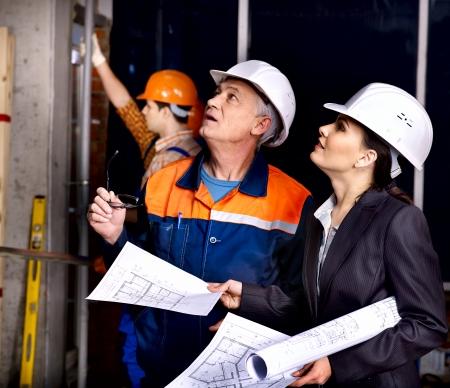 construction project: Business woman in builder helmet indoor.