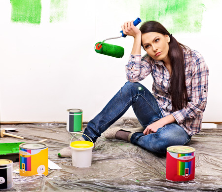Unhappy woman paint wall at home. Imagens
