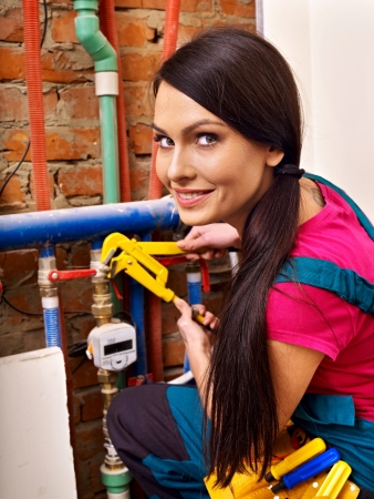 appliances: Woman  builder fixing heating system with special tool.