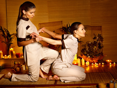 Therapist giving Thai stretching massage to woman. Stock Photo