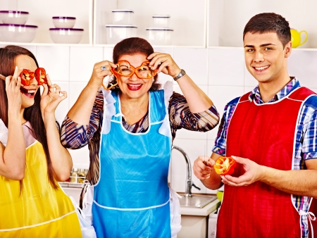 Mature woman with family preparing  dinner at kitchen  photo