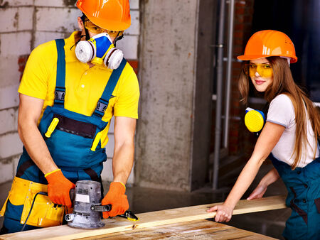 Man and woman in builder helmet with electric planer. photo