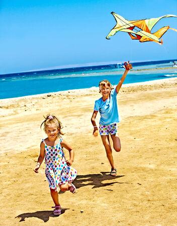 sundress: Child flying kite beach outdoor. Stock Photo