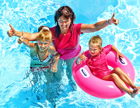 Family with children in swimming pool. Summer outdoor. photo