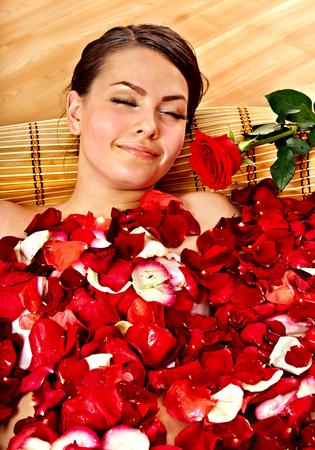 roseleaf: Beautiful young woman in rose petal swim water. Beauty spa.