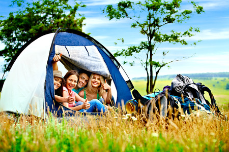 camping equipment: Group people with backpack in tent summer outdoor. Stock Photo