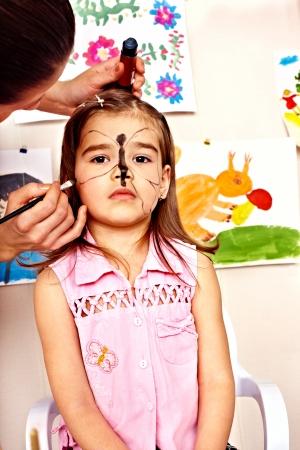 peinture visage: Enfant d'�ge pr�scolaire des enfants avec la peinture faciale. Garde d'enfants. Banque d'images