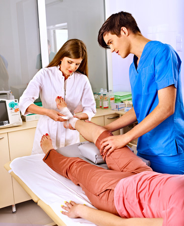 Doctor bandaging patient in hospital. First aid. Stock Photo - 25573180