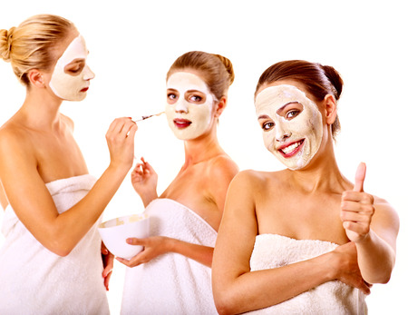 facial spa: Young woman getting facial mask and gossip . Isolated.
