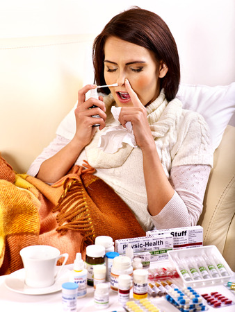 Young woman using throat spray. Indoors