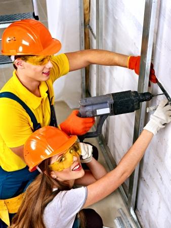 Happy family in builder uniform indoor. photo