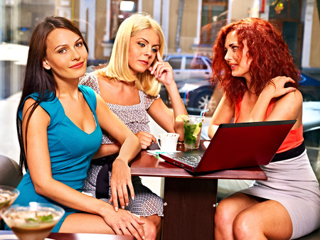 Three young women at laptop drinking coffee in a cafe. photo