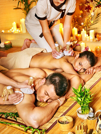 Man and woman getting herbal ball massage in bamboo spa. photo