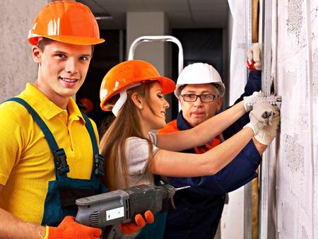 Happy group people in builder uniform indoor. photo