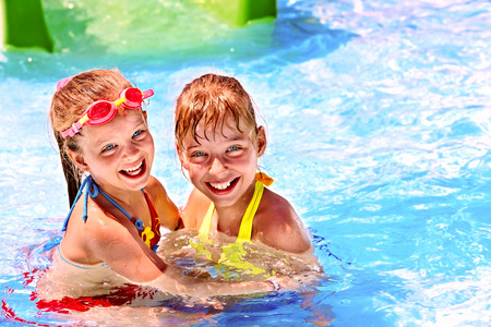 bikini pool: Children on water slide at aquapark. Summer holiday. Stock Photo
