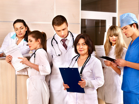 Group doctors and patient standing at reception in hospital. Stock Photo - 25974134
