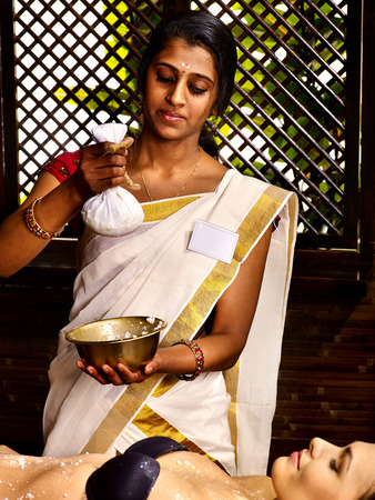 panchakarma: India woman taking massage  pouch of rice. in spa
