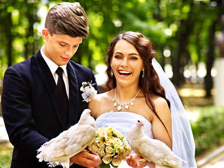 Bride and groom holding dove in park outdoor. photo