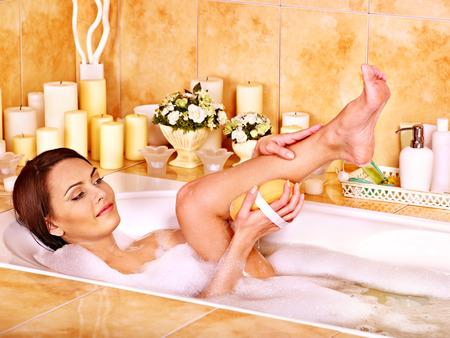 wisp: Young woman wash leg in bathtube.