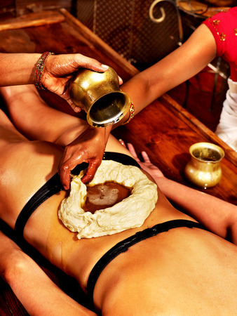 treatment: Young woman having stomach Ayurveda spa treatment. Stock Photo