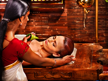 touching noses: Woman having nose ayurveda spa treatment.