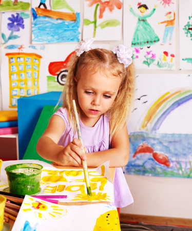 Child painting at easel in school. Imagens