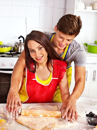Young happy family cooking at kitchen. photo