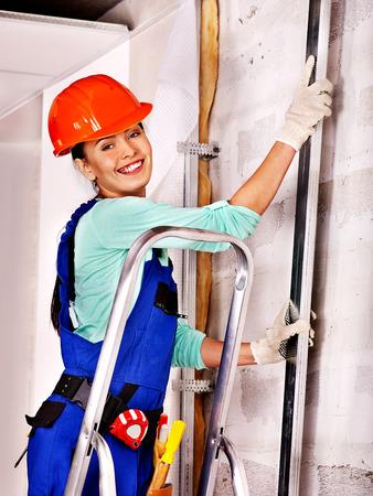 foremaster: Happy woman in builder uniform indoor. Stock Photo