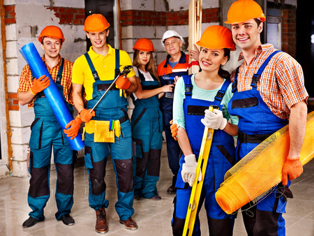 craftsmen: Happy group people in builder uniform.
