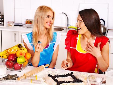 Young women  baking cookies in oven. photo