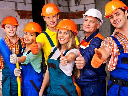 Happy group people in builder uniform thumb up. photo