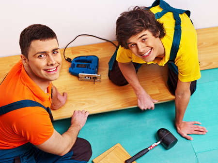 Happy men laying parquet at home. photo