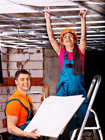 suspend: People in builder uniform installing suspended ceiling