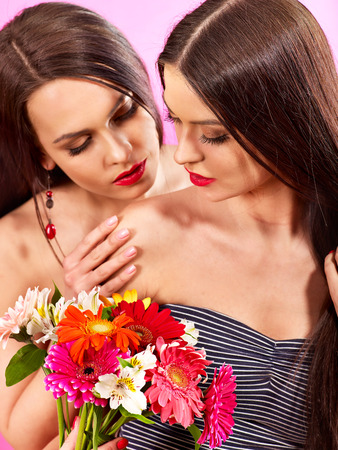 Two sexy lesbian women with flower. photo