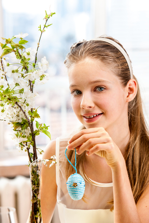 Happy beauty child hang easter egg on cherry branch. photo