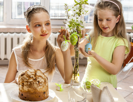 Happy children hang easter egg on cherry branch. photo