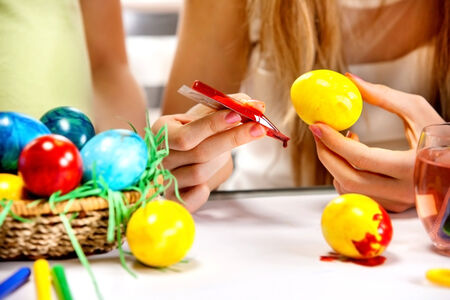 Children paint Easter eggs at home. Focus on hands photo