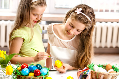 kids club:   Happy children paint Easter eggs at home.
