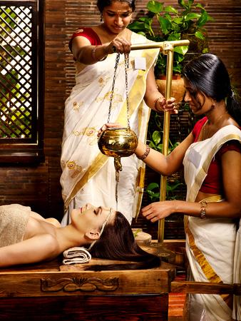 window treatments: Young woman having oil Ayurveda spa treatment. Stock Photo