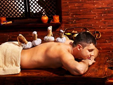 herbal massage ball: Man  having oil Ayurveda spa treatment.