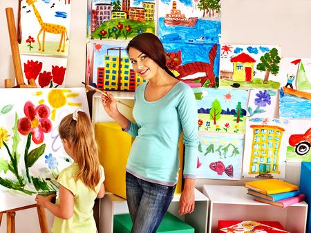children painting: Happy children  with teacher painting. Stock Photo