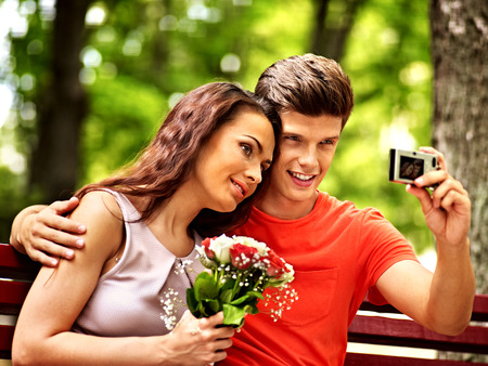 Couple with camera take pictures on bench. Outdoor. photo