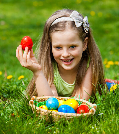 Happy child find easter egg outdoor. photo